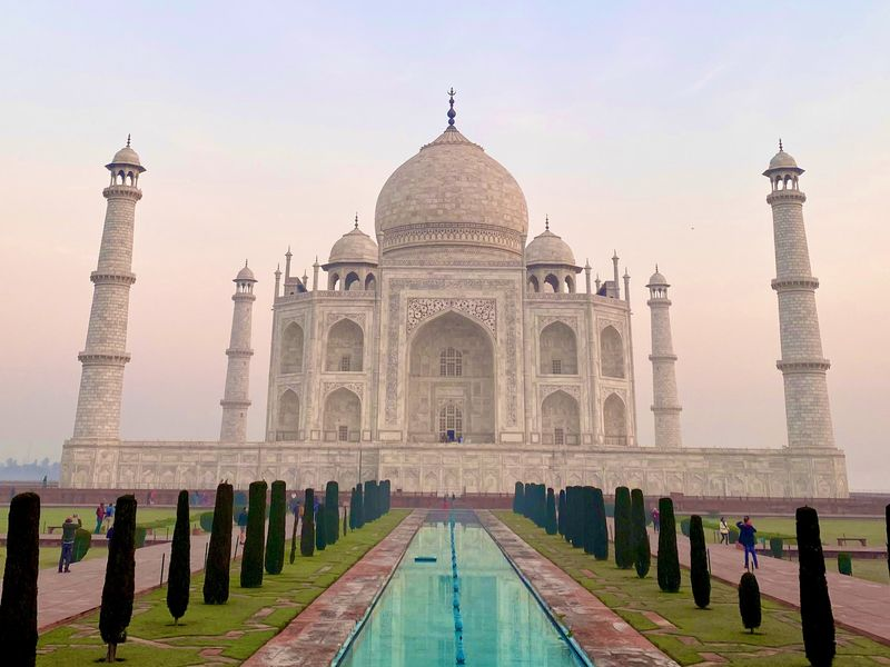 the taj mahal and the reflecting pool in front of it at sunset