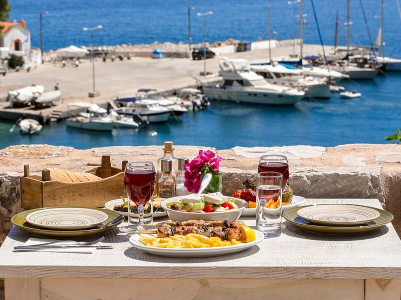 table set for a traditional greek meal overlooking a harbor with boats