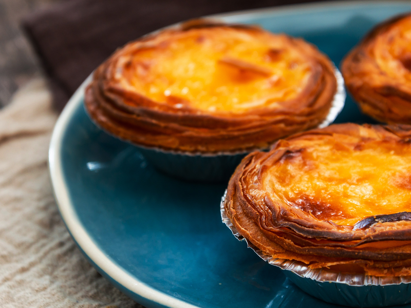 three pasteis de nata or Portuguese custard tarts on a blue plate