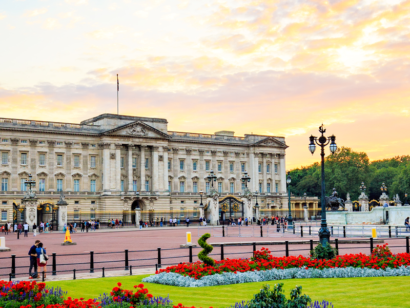 buckingham palace with the sun setting behind it