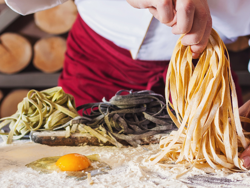 a chef making pasta by hand on a floured kitchen surface