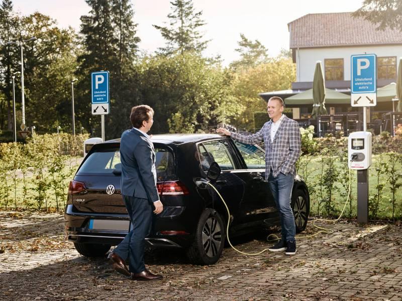 Men talking in front of a car
