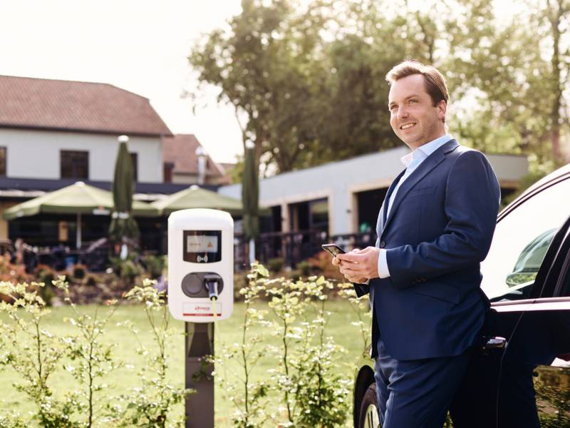Man standing next to the charging station