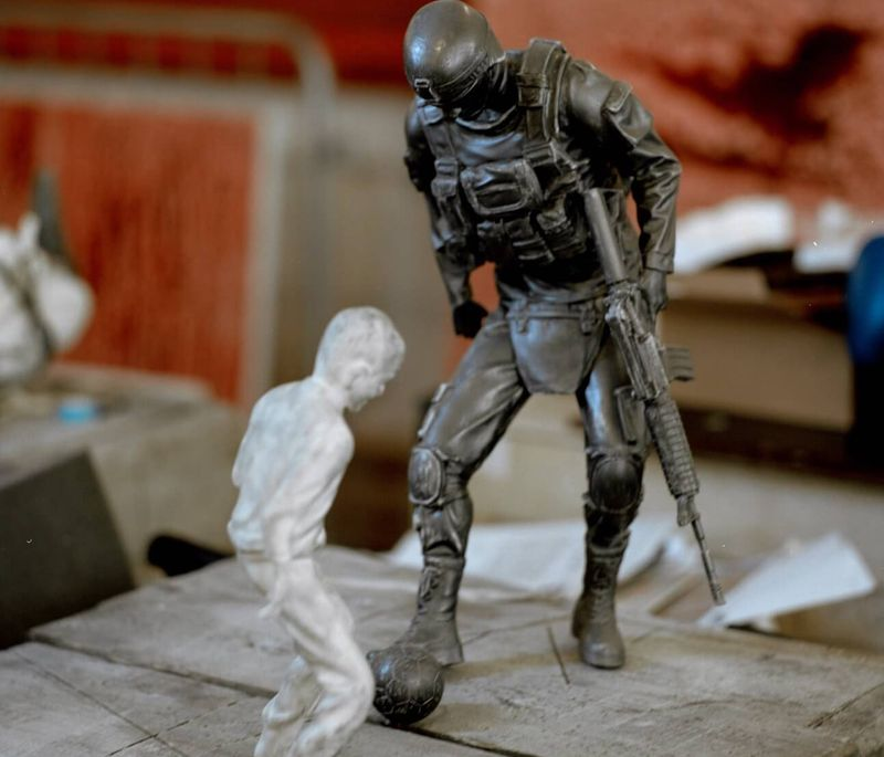 two small figurines of a solider playing football with a child