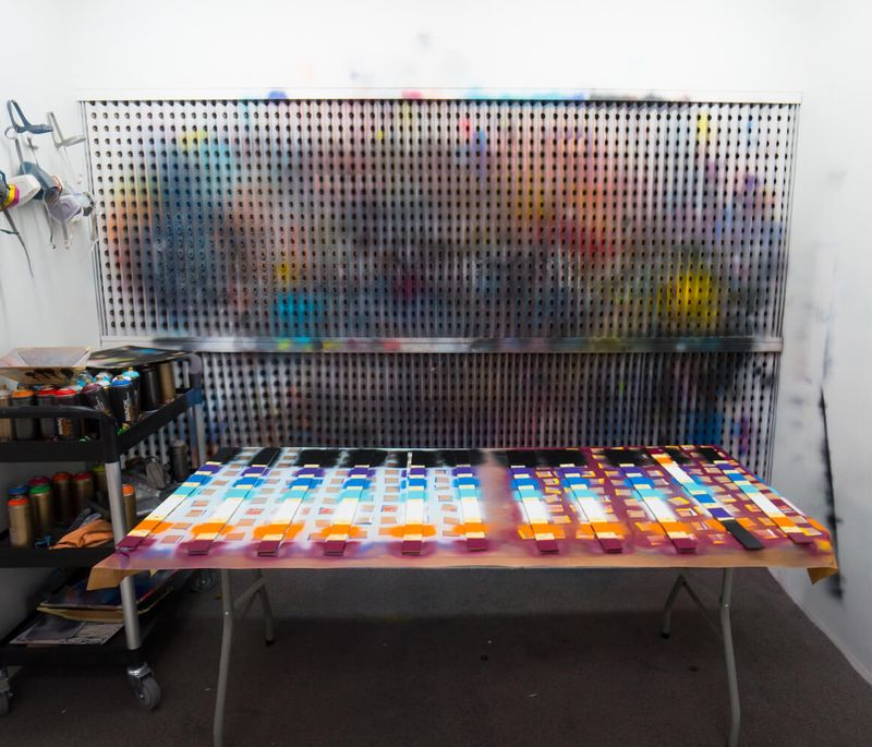 rows of colours and paints lined up on a surface in the artist's studio