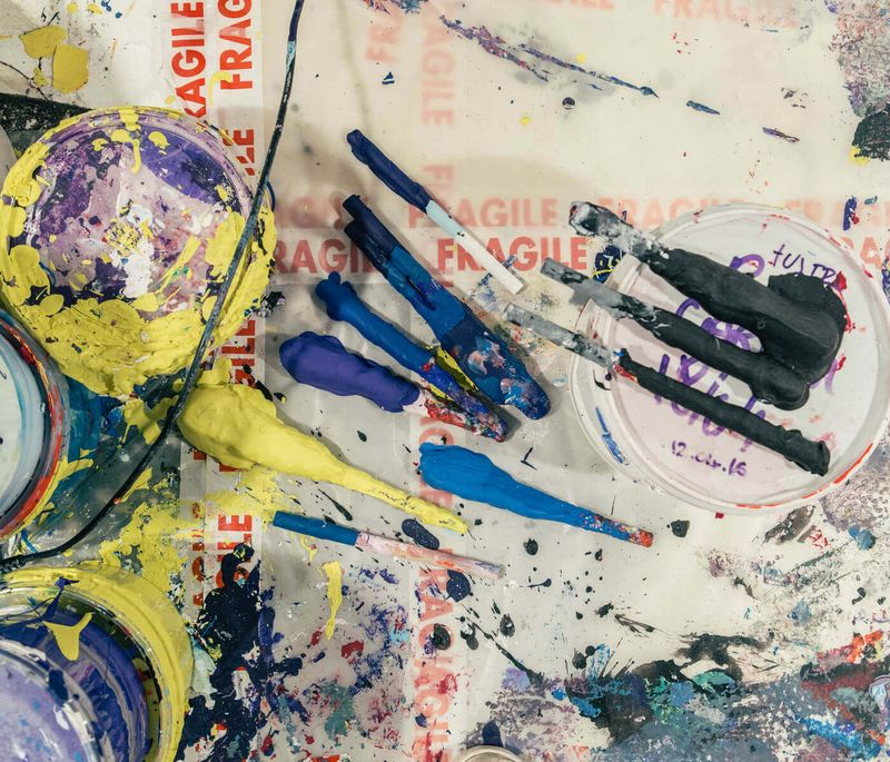 bird's eye view of four pots of paint with a variety of tools and paint splashes next to them