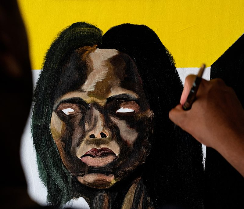 Close-up of a Marcus Brutus painting and the artist's hand as he adds details to black hair