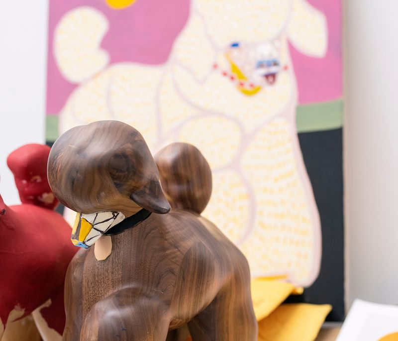 sculpture of poodle in front of larger painting of pink poodle