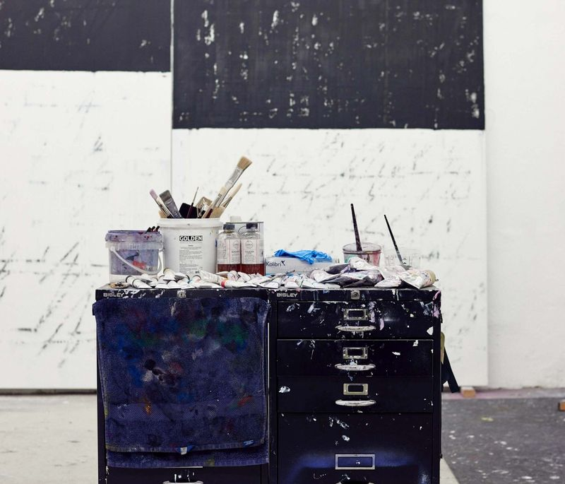 storage unit on wheels in artist's studio with two large canvases behind and paint splashes on the floor