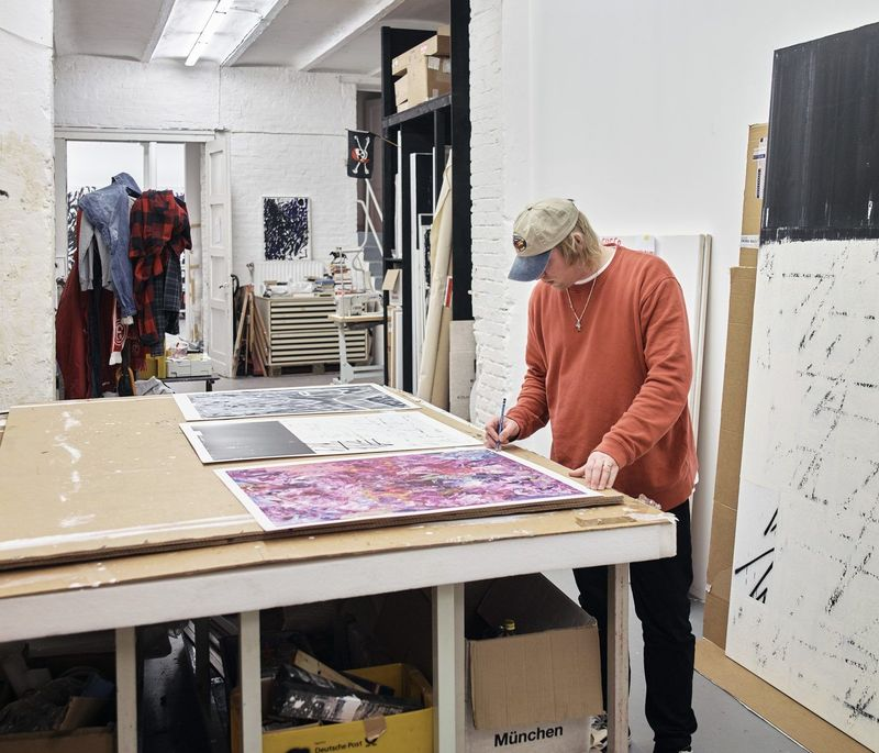 Chris Succo signing artworks that rest on a large table surface in his studio