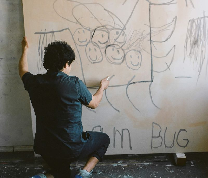 Robert Nava kneeling to hold the side of a large canvas in front of him