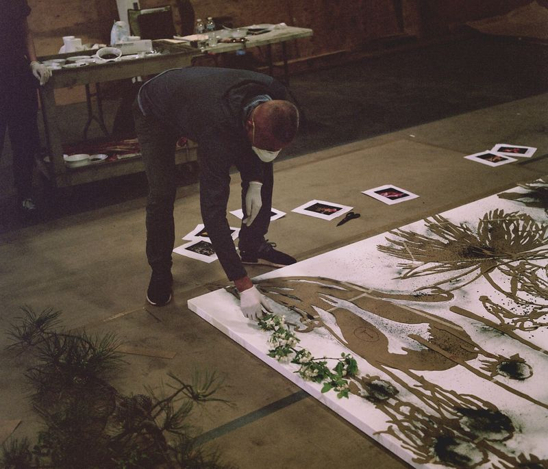 artist bending down to hold a flower up to a large wooden canvas with outlines of flowers and plants on it