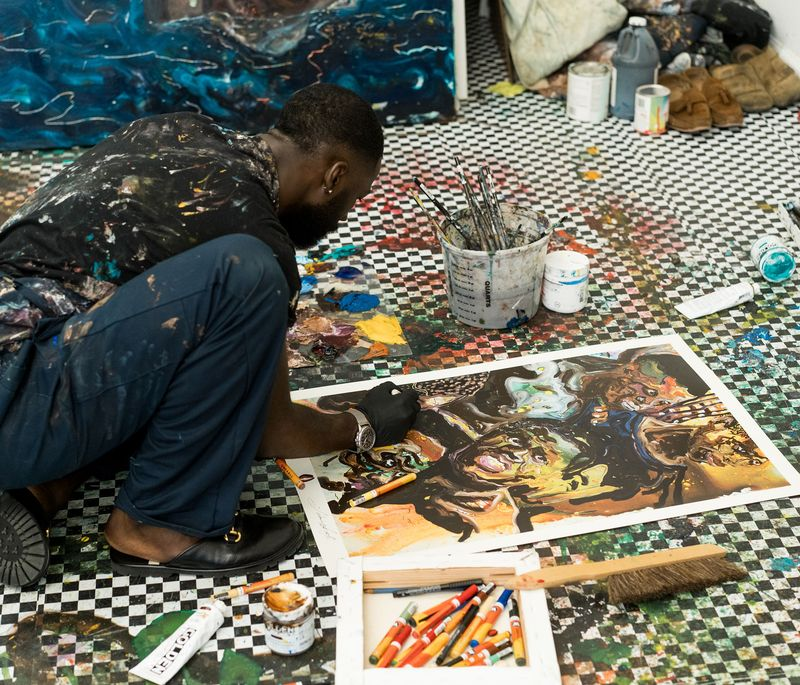 Ludovic Nkoth crouching on the floor surrounded by paints and pens as he adds details to a painting on the floor