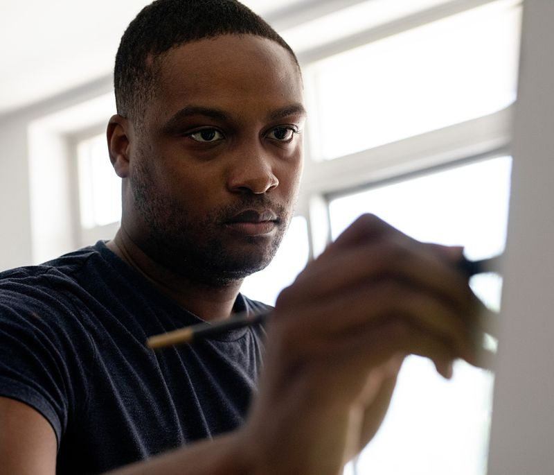 Marcus Brutus concentrating on a painting in front of him and holding a brush