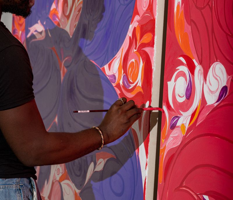 Tunji Adeniyi Jones holding a paintbrush up to two large canvases with red and blue paint