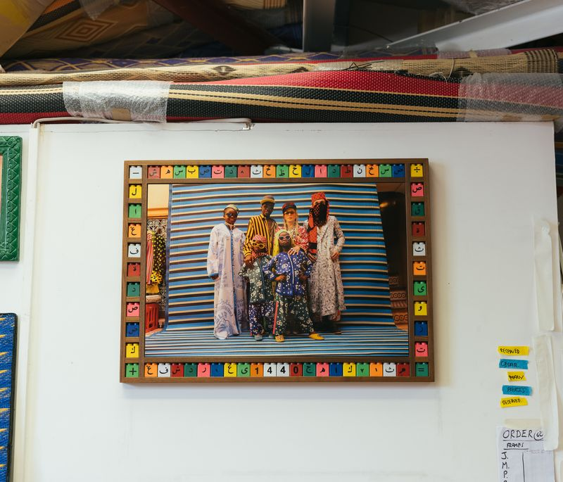 wall of artists studio with three photographs on and colourful framing