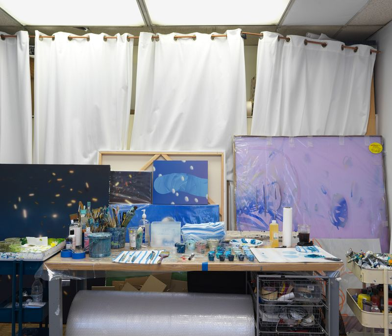 paintings on canvases stacked in front of one another behind a table of artistic tools and materials