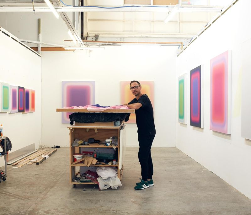 artist Jonny Niesche stands by a wall in his studio