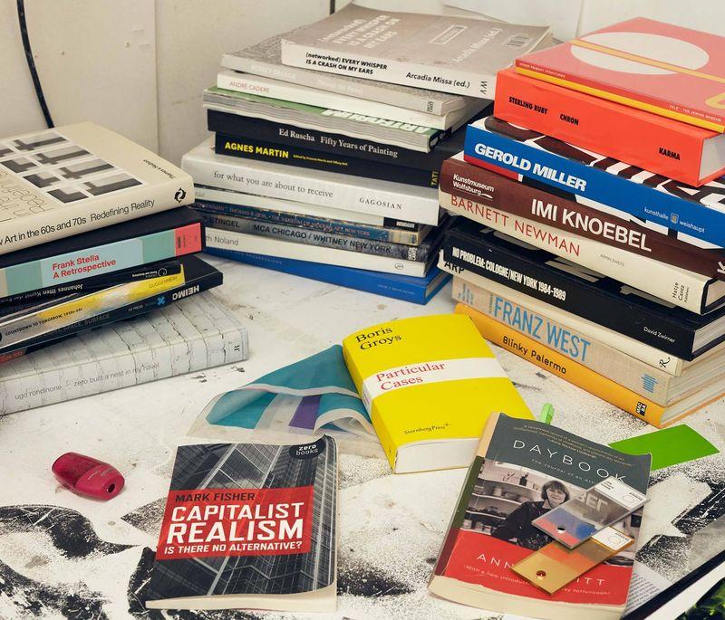 books on a desk in the artist's Jonny Niesche studio - close up shot