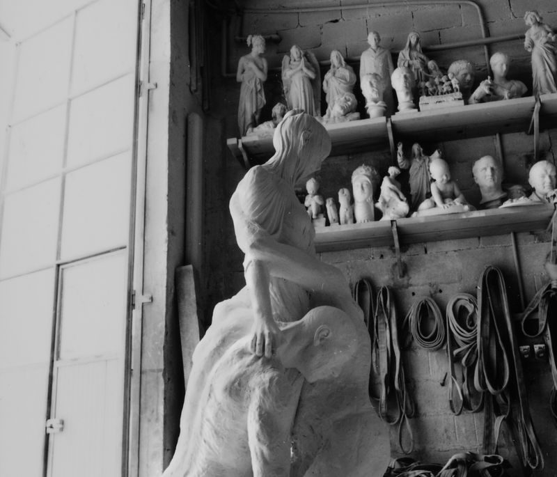 large marble sculpture of three intertwined bodies, with two rows of smaller sculptures on shelves behind them