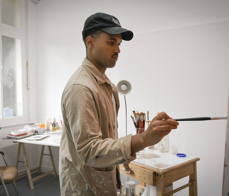 artist concentrates as he holds a paintbrush up to a painting on an easel in front of him in his studio