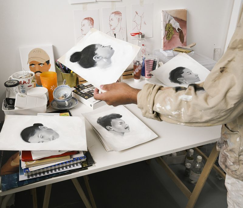 artists desk in his studio with notebooks, sketches and pots on it, as his hands hold up a monochrome painted portrait of a woman