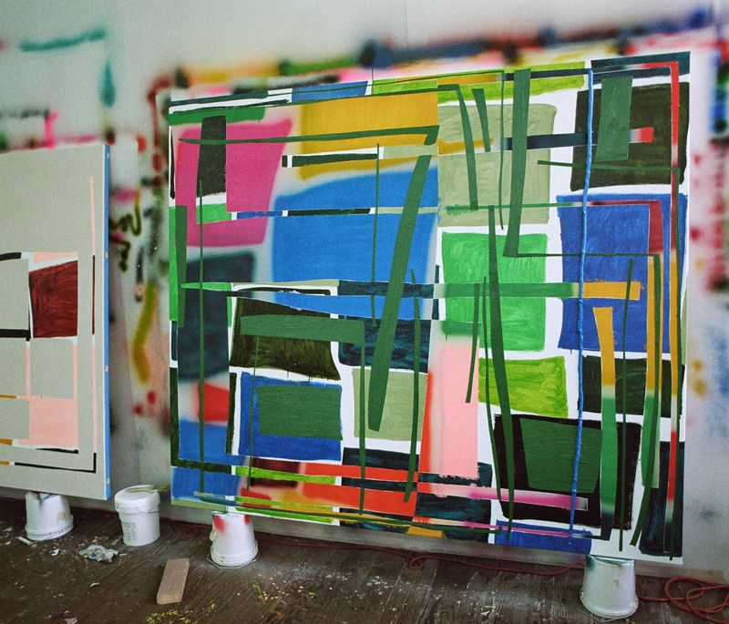 large rectangular painting balanced in the artist's studio of colour blocks and lines