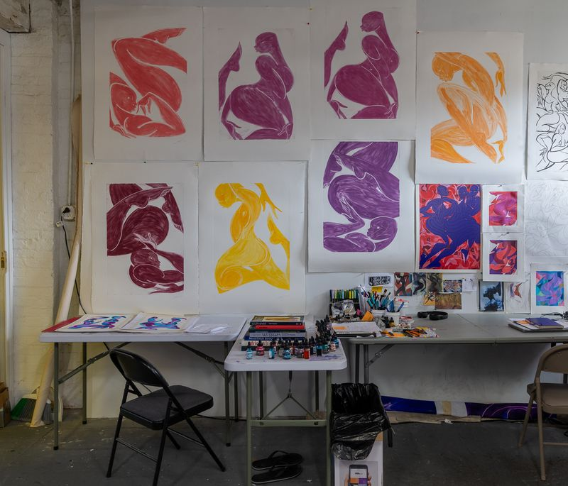 Artist's studio with nine large works on paper taped to the wall above a desk