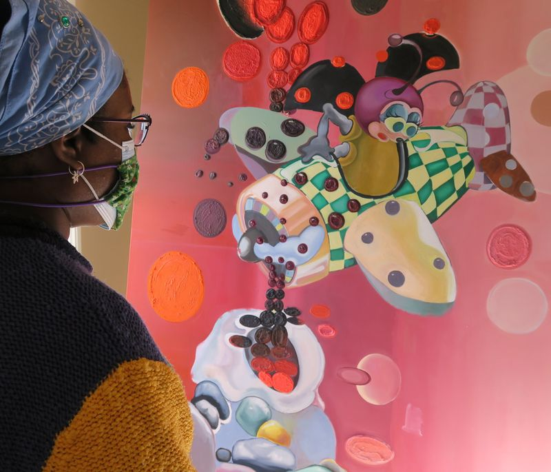 Alake Shilling side profile shot stood gazing upon a pink painting of a ladybug in a plane