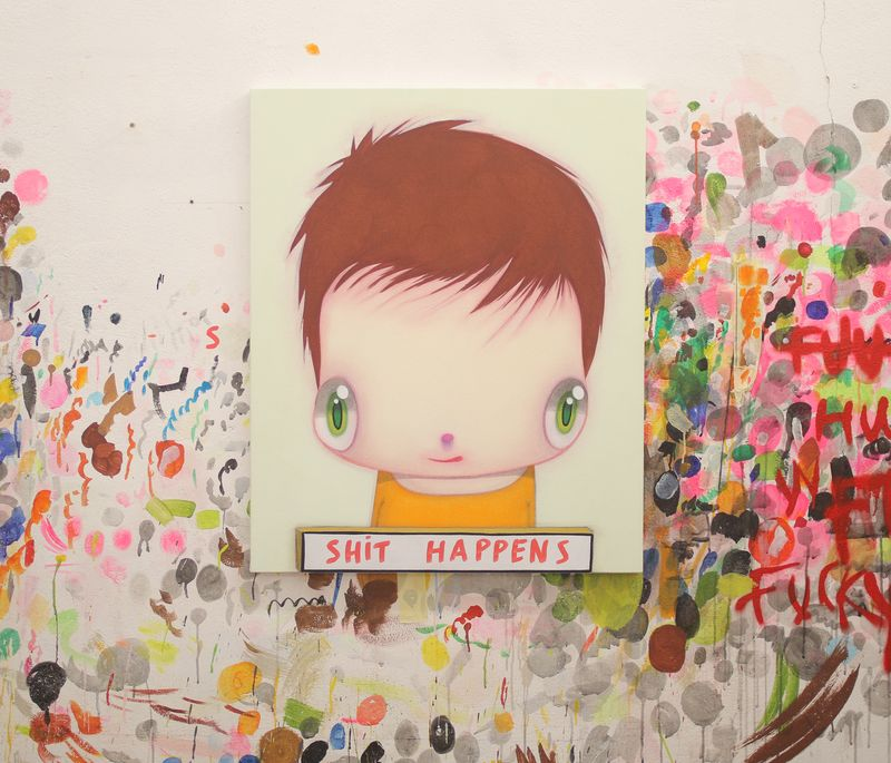 Painting of large-eyed cartoon child placed centrally on a white surface surrounded by splashes of paint and scribbles
