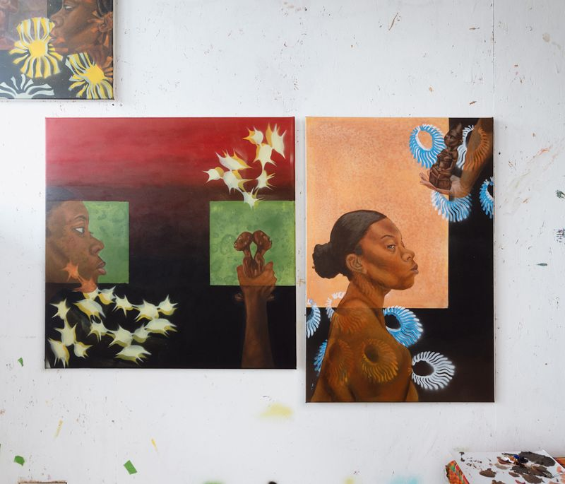 Two small paintings placed against a white surface in the artist's studio