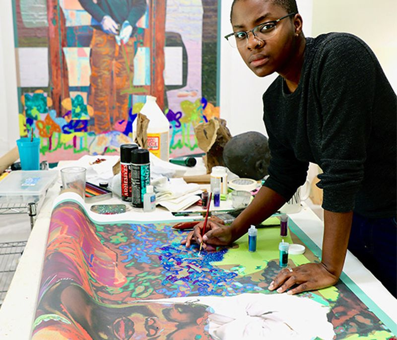 Amani Lewis stood over a large painting which they hold a paintbrush to as they look to the camera