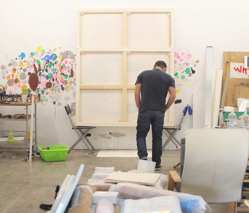 Javier Calleja in his studio standing before a large blank canvas with his back turned to the camera