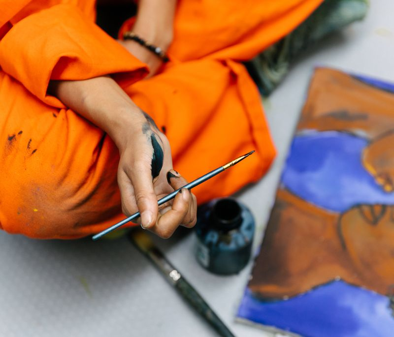 Artist sitting cross-legged on the floor holding a paintbrush dipped in black paint with a painting in front of her