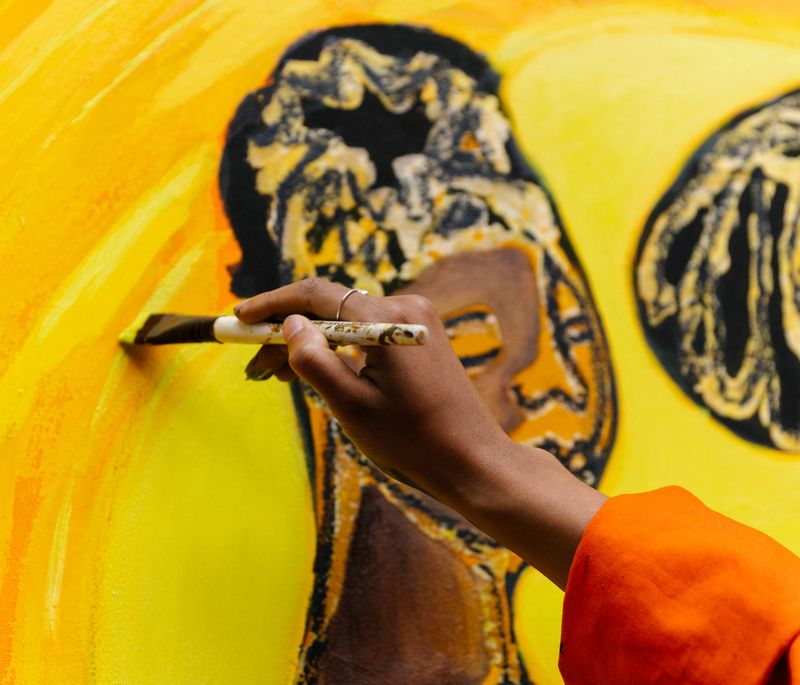 Artist holding paintbrush up to add details to a yellow painting with two figures on it