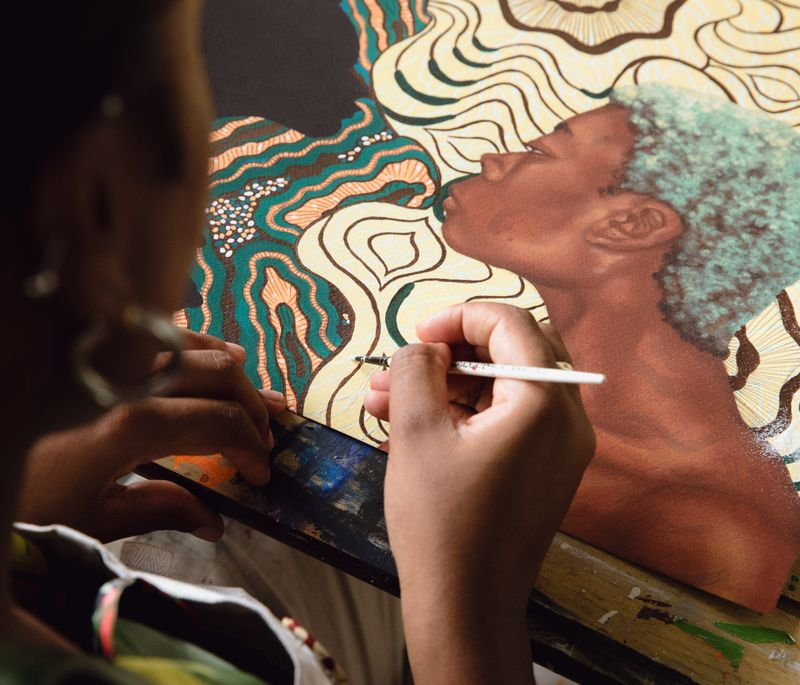 Artist holding a paintbrush to a painting that rests on a table in front of her
