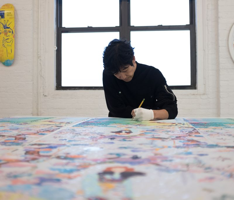 artist in studio signing multiple prints