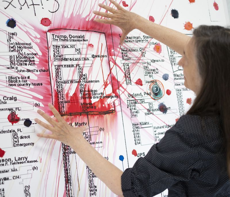 Jenny Holzer holding her hands up to frame a large textual artwork with a rectangle outlined in red on it