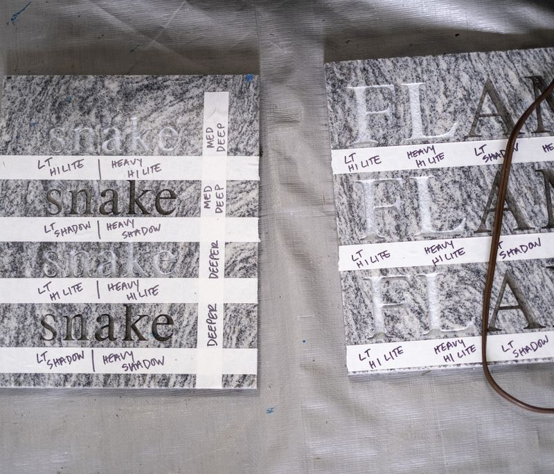 two grey works of art with repeated words engraved into them and white tape creating various lines across them