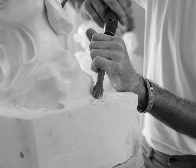 close-up of artist using a tool to chip away and carve out a marble sculpture from the block