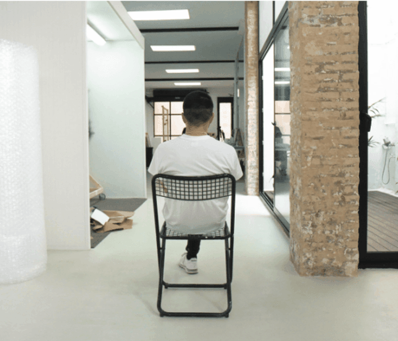 Felipe Pantone sat on a chair facing away from the camera