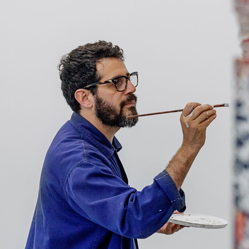 artist wearing blue shirt and glasses holding a long paintbrush in one hand and a paint palette in the other