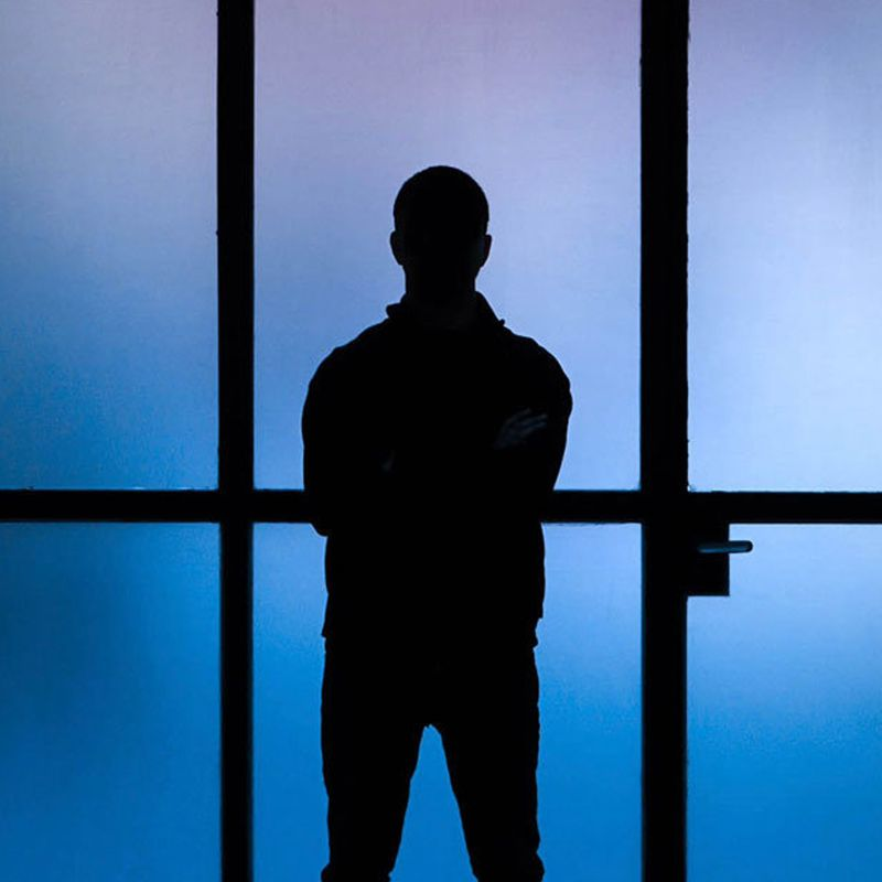 silhouette of Felipe Pantone with blue lit panes of glass behind him