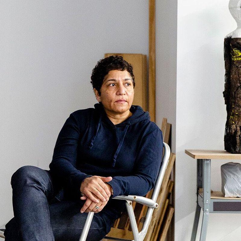Huma Bhabha sat on a chair looking into the distance
