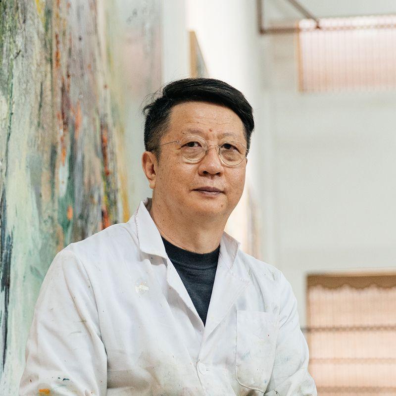 Wang Yan Cheng smiling wearing glasses and a white laboratory coat