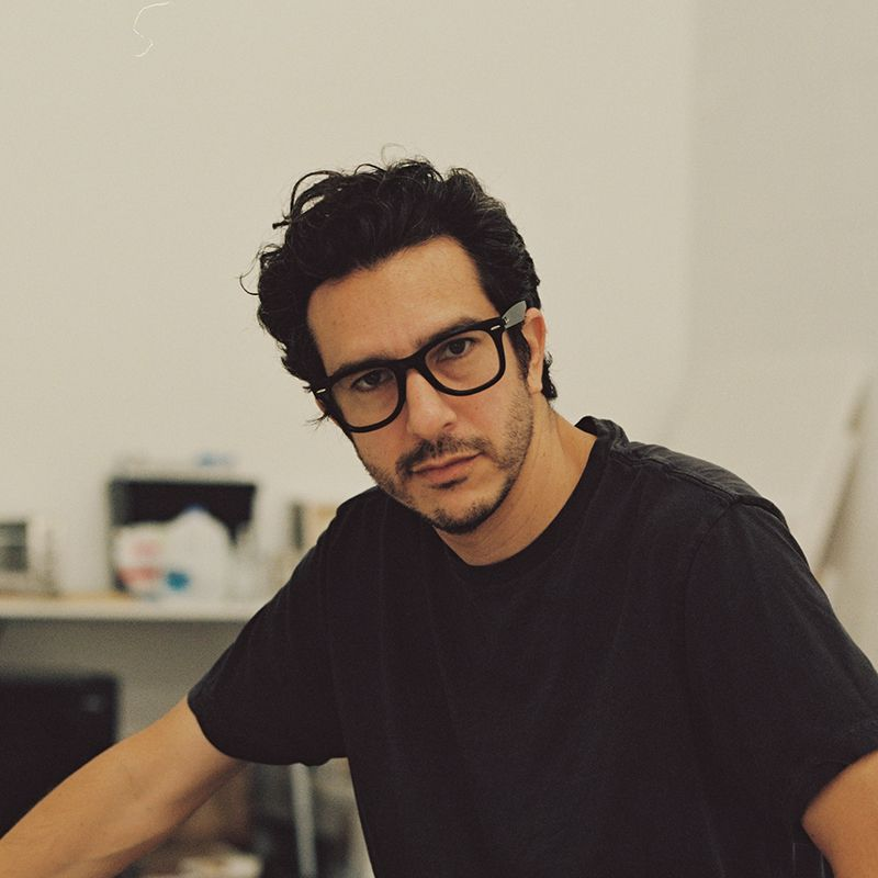 Alejandro Cardenas looking directly into the camera wearing black tshirt and thick-framed glasses