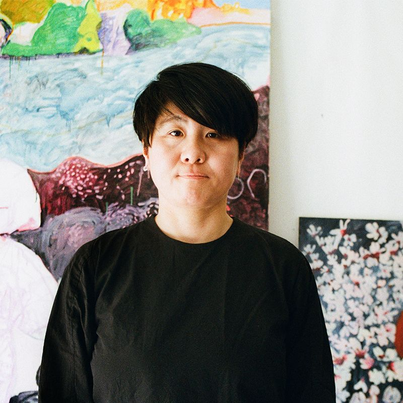 Makiko Kudo smiling with paintings behind her