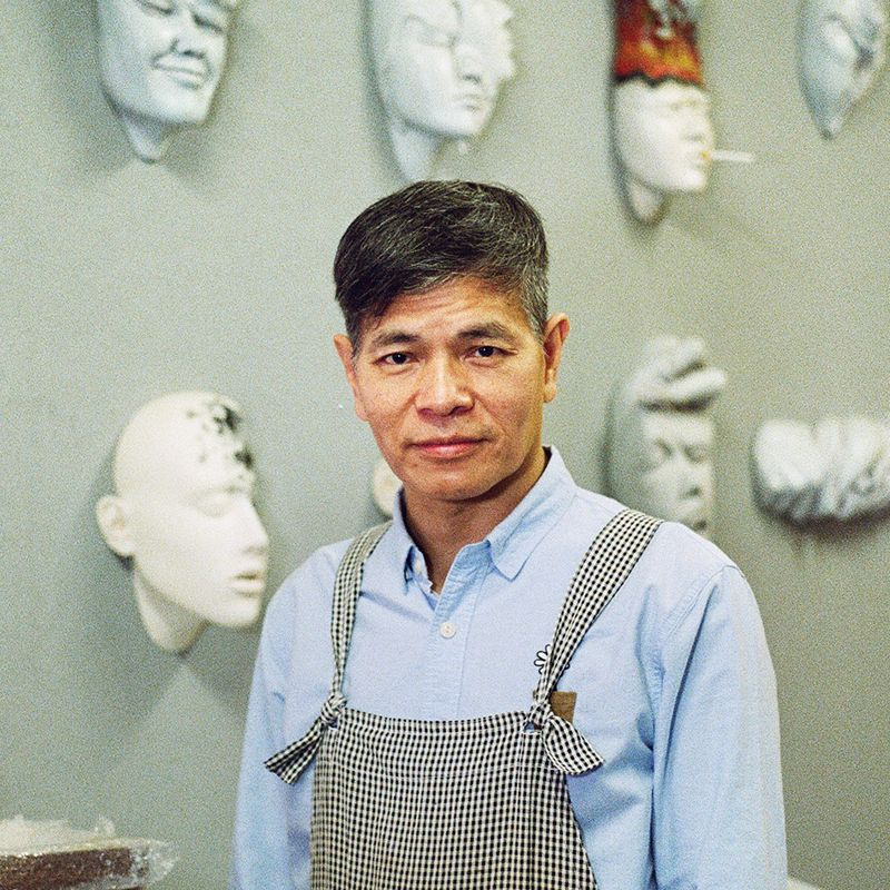 Johnson Tsang looking towards the camera with several of his sculpted heads behind him