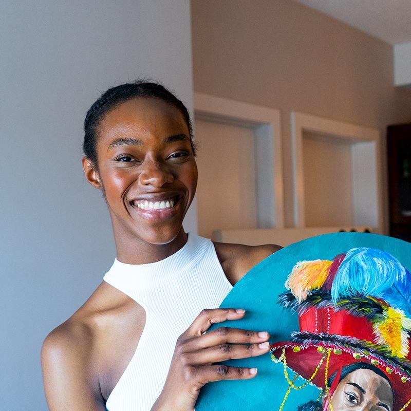 Ekene Manduka smiling and holding a tondo painting