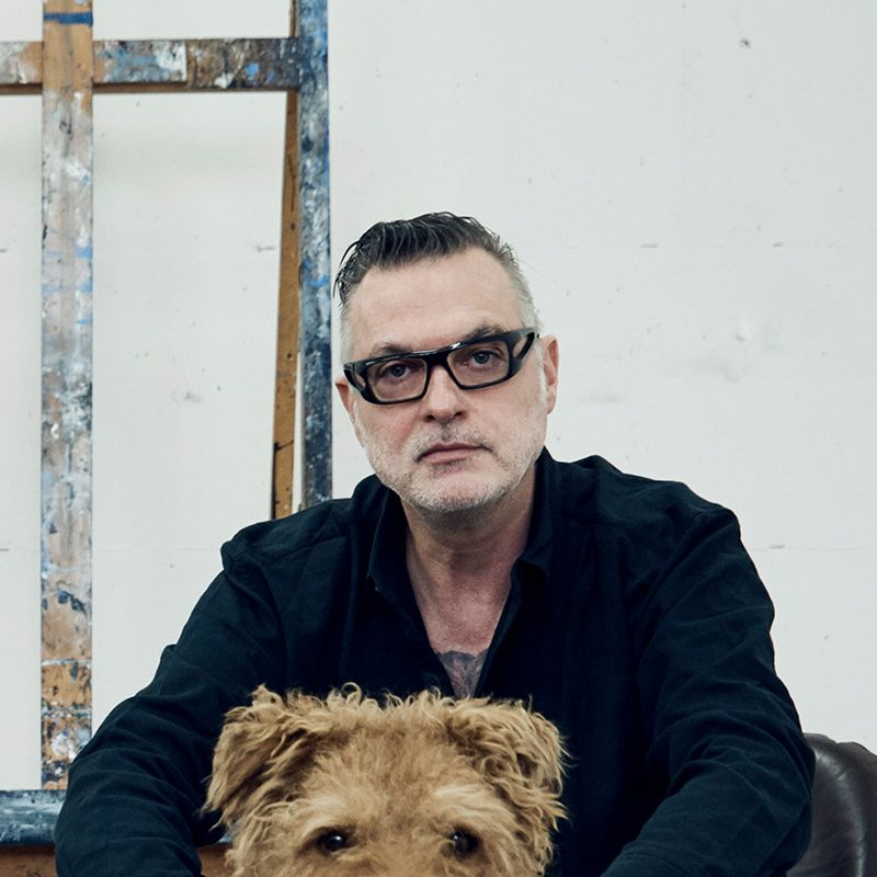 Artist sat in a black jacket with his dog looking directly to the camera